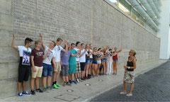 Schüler stehen vor einer Mauer