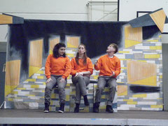 Drei junge Menschen sitzen auf einer Bühne