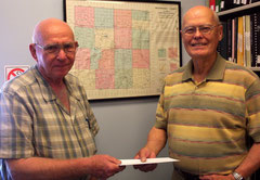 Dick Jackson, left, presents a gift to the cemetery sign project sponsored by the McDonough County Historical Society, represented by Louis Battin, president. The map behind them locates the 110 cemeteries in our county.