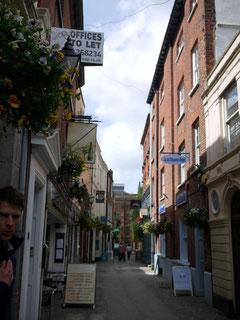 エクセターのメインストリートからはずれた小さな通りとギャングスター(左手前)