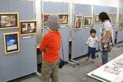 JICAボランティアの活動写真を見入る来場者