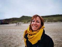 Portraitbild von Stefanie Junius, lachende Frau am winterlichen Strand, senfgelber großer Schal, rötliche Haare