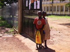 """妨害事件の現場!!ガバメントの敷地全体がフェンスで囲まれ、この門だけが唯一の出入り口に。""""妨害者""""には絶好の機会到来!?! 写真の二人は支援就学中のAwekoとPriska.学校休暇中は、ハダシで1時間以上徒歩で来館。寺子屋組と一緒に午前クラスで学習、3学期に備えます!背後の白い建物は県庁。我らが図書館はこの裏です。"""