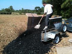 Damien répand le charbon de bois.