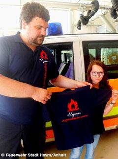 Stellv. Jugendwart Jens übergibt an Mara ein Shirt.