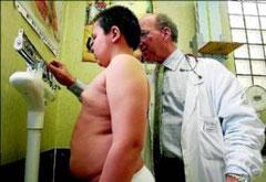 Un médico controla el peso de un niño en una revisión endocrinológica. Foto:AFP PHOTO