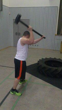 Workout mit Gym-Hammer und Reifen