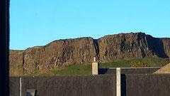 アパートの窓から見えたアーサーズ・シート。でかい岸壁が丘の上に続いています。