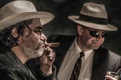 Zwei Männer mit Hut und Zigarre