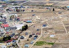 【写真㊦=がれきの撤去がほぼ終了した野田村中心部(左端の赤い屋根が野田村役場)=16日】