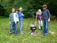 Schulkinder am Suppe und Wurst abkochen