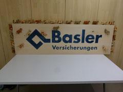 Geschnitzes und bemaltes Logo umrahmt von Holzkühen