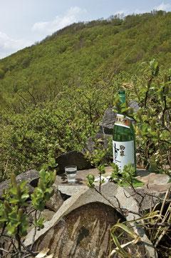取材隊から神酒が捧げられた。後方の山はドコノ森(八合目付近)