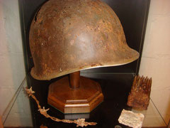 US M1 combat helmet together with a 30-06 caliber clip for the M1 Garand  all found in Ste. Marie-du-Mont as well as a fragment for coffee ration which came from Utah Beach