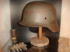German M40 combat helmet found in Ste. Marie-du-Mont, related to a soldier of Grenadier Rgt. 919. The 13./Grenadier Rgt. 919 was in Brucheville. Also on the photo are a relic belt buckle also from Ste. Marie-du-Mont as well a part of a machine gun belt an