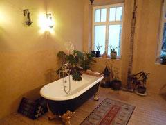 Gleicher Wohnraum nachher: jetzt Badezimmer mit freistehender Gußbadewanne auf Holzboden