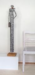 Große, schlanke Skulptur aus Pappmache mit Koffer und Schal auf Reisen  - montiert auf geölten Sockel aus stabverleimter Eiche -  Größe ca. 118 cm