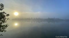 Sonnenaufgang am See, die Wasseroberfläche raucht
