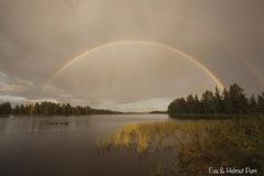 Doppelter Regenbogen spiegelt sich im See