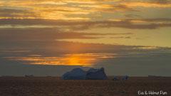 Eisberg im Südpolarmeer - untergehende Sonne taucht Meer und Himmel in Rot