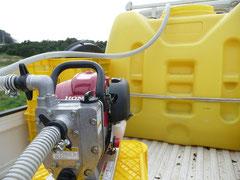 小さいエンジンポンプで給水中。奥は800リットルのタンク。
