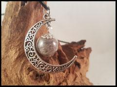 Bild 2: Glasperle gefüllt mit Haaren an einem silbernen Halbmond angebracht. Preis: 28 Euro