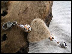Bild 16: Ein Fellhrz mit Porzellanperlen und verschiedenen farbiegen anderen Elementen aus Acryl, als Abschluss ein silberner Pfotenanhänger. Preis: 36 Euro