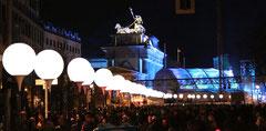 Lichtergrenze bei Nacht vor dem blau erleuchteten Brandenburger Tor und Quadriga. Foto: Helga Karl