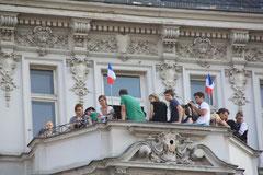 Zuschauer beim Umzug Karneval der Kulturen Berlin auf einem Stuck-Balkon mit französischen Fähnchen. Foto: Helga Karl