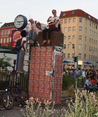Junge Männer sitzen auf einem Podest, die große Uhr daneben zeigt die falsche Zeit 9.15 am Nachmittag beim Umzug Karneval Berlin. Foto: Helga Karl