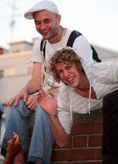 Zwei junge Männer winken fröhlich in die Kamera. Karneval Umzug Pfingsten Berlin. Foto: Helga Karl