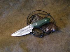 Couteau plate semelle, longueur totale 12,2cm, lame 6,5cm. Acier 440A. Côtes en micarta vert. Gravure à l'eau-forte. Etui kydex recouver de peau d'iguane.