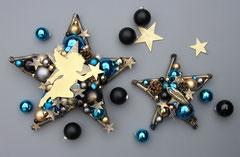 Dekorvorschlag: Großer und kleiner Stern in den Farben schwarz - gold - blau vor einem grauen Hintergrund mit goldenen Sternen und Glaskugeln kombiniert.