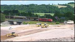 Am 24.06.2010 zieht eine Lok der BR 155 den VW-Zug, im Vordergrund die Baustelle zur Einbindung der Ortsumfahrung Flöha in die B 173 bei Niederwiesa.