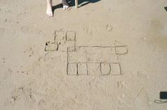 温はひろったゴミで砂浜に字を書いています。四角い箱で書いた「フレーミー」(ピタゴラスイッチに出てくる犬)。