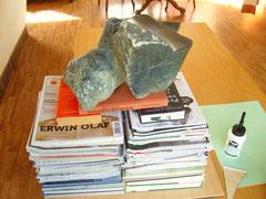 Een triplexplaat wordt ingesmeerd met houtlijm, op de achterzijde van het mozaiek geplaatst en aangeperst met boeken, tijdschriften en een blok steen
