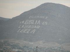 国境の橋から見える山の文字。「聖書は真実なり。読みなさい」とある。