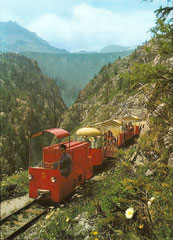 Der Zug mit der Staumauer im Hintergrund