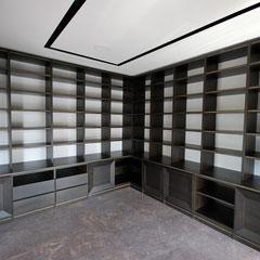 Libreria in rovere wengè. Bordatura con profili bronzo.