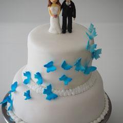 Hochzeitstorte mit blauen Schmetterlingen und Hochzeitspaar aus Zucker