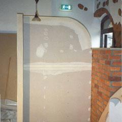 Einfache aus Sperrholz gebaute Trennwand soll eine Backsteinwand werden.