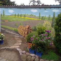Der Wunsch wird wahr gemalt:  Weg und Holzstoß gehen weiter. Die dazu weit gemalte Landschaft macht nun den kleinen Garten größer.