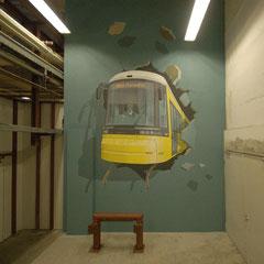 Die Straßenbahn durchbricht die Wand.
