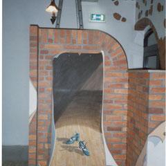 Trennwand wurde malerisch verwandelt als Backsteinwand mit gemaltem Poster auf dem tanzende grüne Schuhe zu sehen.