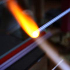 Das Glas wird langsam in der Flamme geschmolzen bis es die Konsistenz von Honig hat.