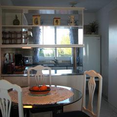 Küche mit gemütlicher Sitzecke an großem Glastisch