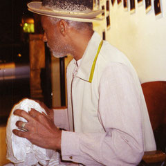 David Hammons holding nappy rock/and nappy hat