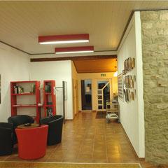 Das Entree mit Blick zum Ausgang.Sitzecke mit kleiner Bibliothek, dahinter Garderobe, Toiletten. Links die Teeküche.