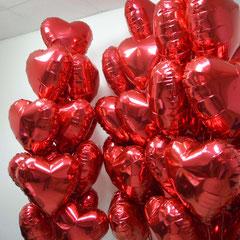 красные фольгированные сердца, наполненные гелием