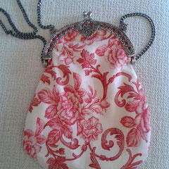 Bolso beige con estampados coral oscuro y boquilla labrada.